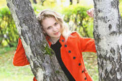 Beautiful woman standing near the birch-trees. Young beautiful blonde woman standing near the birch-trees Royalty Free Stock Photos