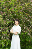 Beautiful woman standing near blooming apple tree Stock Image