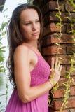 Beautiful woman standing near brick wall Stock Photo