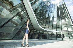 Beautiful  woman standing near the building of the business center. Beautiful young woman standing near the building of the business center Royalty Free Stock Images