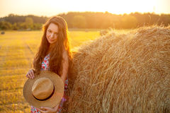 Beautiful woman standing near a hay bale in field. Royalty Free Stock Photos