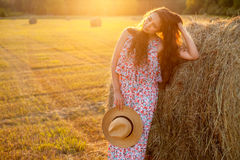 Beautiful woman standing near a hay bale in field. Royalty Free Stock Image