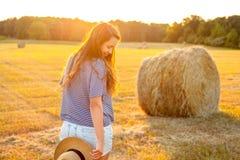 Beautiful woman standing near a hay bale in field. Stock Image