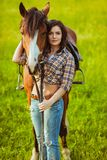 Beautiful woman standing near a horse stock image