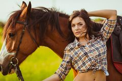 Beautiful woman standing near a horse Stock Photography