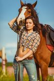 Beautiful woman standing near a horse Royalty Free Stock Images