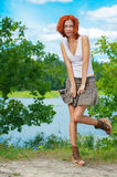 Beautiful woman standing near lake Stock Photo