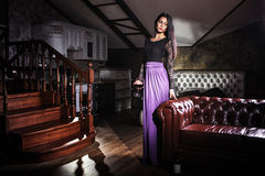Beautiful woman standing near leather vintage sofa Stock Images