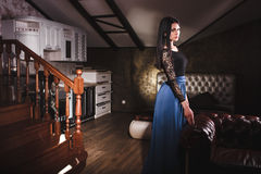 Beautiful woman standing near leather vintage sofa Royalty Free Stock Images