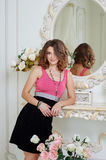 Beautiful woman standing near mirror in the luxurious interior Stock Photo