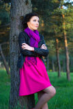 Beautiful woman standing near the tree in summer forest Royalty Free Stock Photo