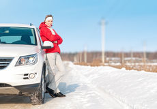 Beautiful woman standing near white car in winter. Stock Photography