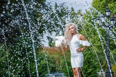 Beautiful woman standing next to the fountain, summer mood stock image