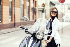 Beautiful woman standing next to his motorcycle royalty free stock photography