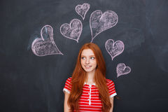 Beautiful woman standing over chalkboard with drawn hearts behind her Stock Images