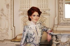 Beautiful woman standing in the palace room. royalty free stock photography