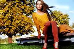 Beautiful woman standing in a park in autumn stock photos