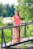 Beautiful woman standing in a park near the bridge Royalty Free Stock Photography