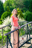 Beautiful woman standing in a park near the bridge Royalty Free Stock Image