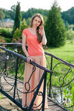 Beautiful woman standing in a park near the bridge Royalty Free Stock Photos