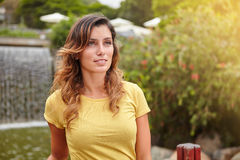 Beautiful woman standing by park waterfall Stock Photo
