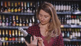 Beautiful woman is standing and reading label of champagne at alcohol department in supermarket. Female customer is taking bottle from shelf for checking on stock video footage
