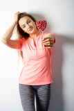 Beautiful woman standing with a red heart candy in the hands Royalty Free Stock Image
