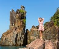 Beautiful  woman standing among the rocks near the sea. Beautiful young woman standing among the rocks near the sea Stock Images