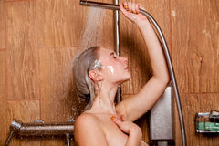 Beautiful woman standing at the shower.  She holds in her hand showerhead Royalty Free Stock Photo