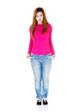 Beautiful woman standing and showing her empty pockets. Royalty Free Stock Photography