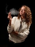 Beautiful woman standing and smoking Stock Images