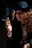 Beautiful woman standing and smoking on the black Stock Image