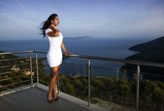 Beautiful woman standing on the terrace. And overlooking the sea Stock Images