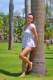 Beautiful woman standing under palm tree Stock Photography