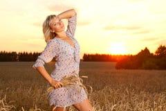 Beautiful woman standing on wheat field Stock Photo