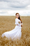 Beautiful woman standing in wheat field Stock Images