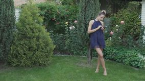 Beautiful woman stands barefoot on grass in garden and messaging on phone. Pretty woman is standing on the background of green trees. Attractive woman uses stock video