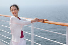 Beautiful woman stands on board of large ship Stock Photo