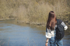 Beautiful woman stands near river, back side royalty free stock images