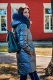 Brunette woman stands under a tree in a park next to a red house. Beautiful woman stands under a tree in a park next to a red house in a winter jacket down Royalty Free Stock Image