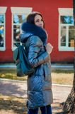 Brunette woman stands under a tree in a park next to a red house. Beautiful woman stands under a tree in a park next to a red house in a winter jacket down Stock Photography