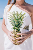 Beautiful woman stands on a white sandy beach by the ocean. A girl in a white dress is holding a yellow pineapple in her hands. A young European long hair woman Stock Photo