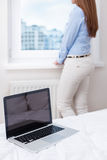 Beautiful woman staring out of window with laptop in foreground Stock Photo