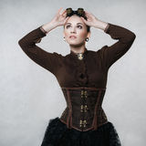 Beautiful woman in steampunk style. On a gray background Royalty Free Stock Images