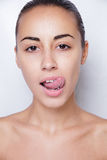 Beautiful woman sticking out her tongue and showing young piercing Royalty Free Stock Photography