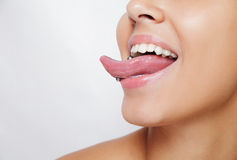 Beautiful woman sticking out her tongue and showing young piercing Stock Photos