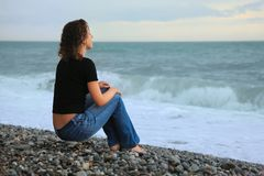 Beautiful woman on stone seacoast, sitting by back Stock Photography