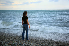 Beautiful woman on stone seacoast, Standing back Stock Image