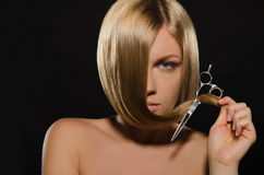 Beautiful woman with straight hair holds scissors Royalty Free Stock Photos