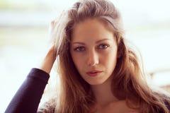 Beautiful woman straightens long dark hair Stock Photos